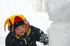 Menino que faz um boneco de neve Fotos de Stock