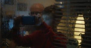 Menino que filma a tempestade através da janela video estoque