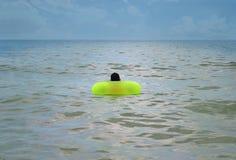 Menino que flutua nas ondas no litoral Fotografia de Stock