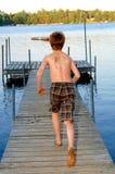 Menino que funciona ao lago Fotos de Stock Royalty Free