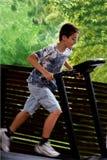 Menino que funciona na escada rolante Foto de Stock Royalty Free