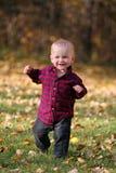 Menino que funciona nas folhas de outono Foto de Stock