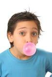 Menino que funde uma goma de bolha cor-de-rosa Fotografia de Stock Royalty Free