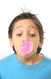 Menino que funde uma goma de bolha cor-de-rosa Foto de Stock
