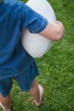 Menino que guarda a bola de rugby Imagem de Stock Royalty Free