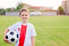 Menino que guarda a bola do futebol no campo de ação Imagens de Stock Royalty Free