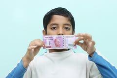 Menino que guarda 2000 dinheiros indianos novos da rupia em sua mão Imagens de Stock Royalty Free