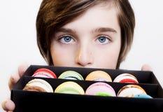 Menino que guarda macarons da sobremesa na caixa de madeira preta Imagens de Stock