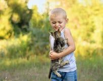 Menino que guarda o gatinho Imagens de Stock