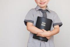 Menino que guarda o livro da Bíblia Sagrada Fotos de Stock Royalty Free