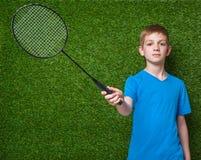 Menino que guarda a raquete de badminton sobre a grama verde Fotos de Stock