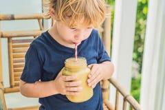 Menino que guarda um batido da banana, conceito apropriado da nutrição fotografia de stock