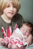 Menino que guarda um bebê recém-nascido imagens de stock royalty free