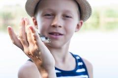 Menino que guarda um peixe frito Foto de Stock