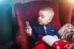 Menino que guarda um trem da meia e do brinquedo do Natal imagens de stock