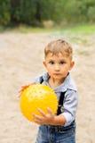 Menino que guarda uma bola amarela em suas mãos Fotos de Stock