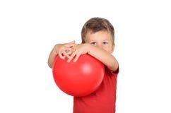 Menino que guarda uma bola vermelha Fotografia de Stock