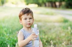 Menino que guarda uma garrafa de água Foto de Stock Royalty Free