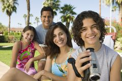 Menino (13-15) que guardara a câmara de vídeo que senta-se fora com irmã (7-9) e retrato dos pais. Foto de Stock
