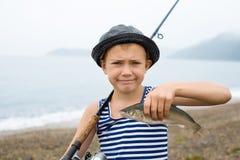 Menino que guardara um peixe foto de stock