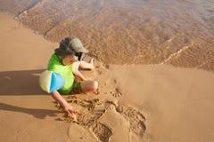 Menino que joga com areia e água em uma praia tropical, vestida no roupa de mergulho protetor, fitas vestindo fotos de stock royalty free