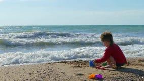 Menino que joga com a areia na praia video estoque