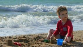 Menino que joga com a areia na praia pelo mar filme