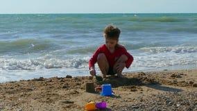 Menino que joga com a areia na praia pelo mar video estoque