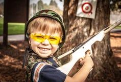 Menino que joga com a arma da besta do brinquedo Imagem de Stock Royalty Free