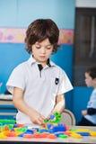 Menino que joga com blocos coloridos na sala de aula imagens de stock