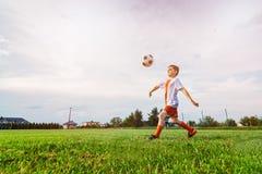 Menino que joga com a bola do futebol no campo de ação Fotos de Stock Royalty Free