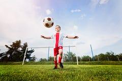 Menino que joga com a bola do futebol no campo de ação Fotos de Stock