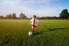Menino que joga com a bola do futebol no campo de ação Foto de Stock