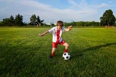 Menino que joga com a bola do futebol no campo de ação Imagens de Stock