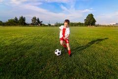 Menino que joga com a bola do futebol no campo de ação Imagens de Stock Royalty Free