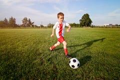 Menino que joga com a bola do futebol no campo de ação Fotografia de Stock
