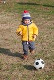 Menino que joga com a bola do futebol ou do futebol esportes para o exercício e a atividade Fotografia de Stock