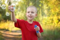 Menino que joga com bolhas Foto de Stock