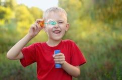 Menino que joga com bolhas Foto de Stock Royalty Free