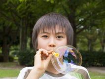 Menino que joga com bolhas de sabão Fotografia de Stock Royalty Free