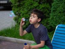 Menino que joga com bolhas de sabão imagens de stock royalty free