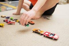 Menino que joga com coleção do carro no tapete Jogo da mão da criança Brinquedos do transporte, do avião, do plano e do helicópte Imagem de Stock Royalty Free