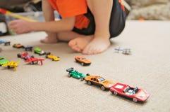 Menino que joga com coleção do carro no tapete Jogo da mão da criança Brinquedos do transporte, do avião, do plano e do helicópte Fotografia de Stock Royalty Free