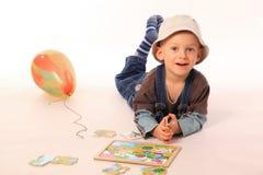 Menino que joga com enigma Foto de Stock
