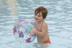 Menino que joga com esfera de praia Imagens de Stock