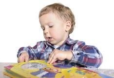 Menino que joga com livro imagem de stock