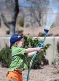Menino que joga com mangueira de jardim Fotografia de Stock