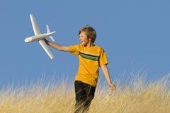 Menino que joga com o avião do planador do brinquedo fotos de stock