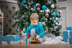 Menino que joga com o brinquedo de madeira do martelo ao sentar-se ao lado da árvore de Natal Fotografia de Stock Royalty Free