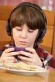 Menino que joga com o console à mão dos jogos Fotografia de Stock Royalty Free